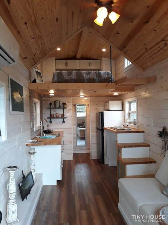 Interior of tiny home including kitchen and loft
