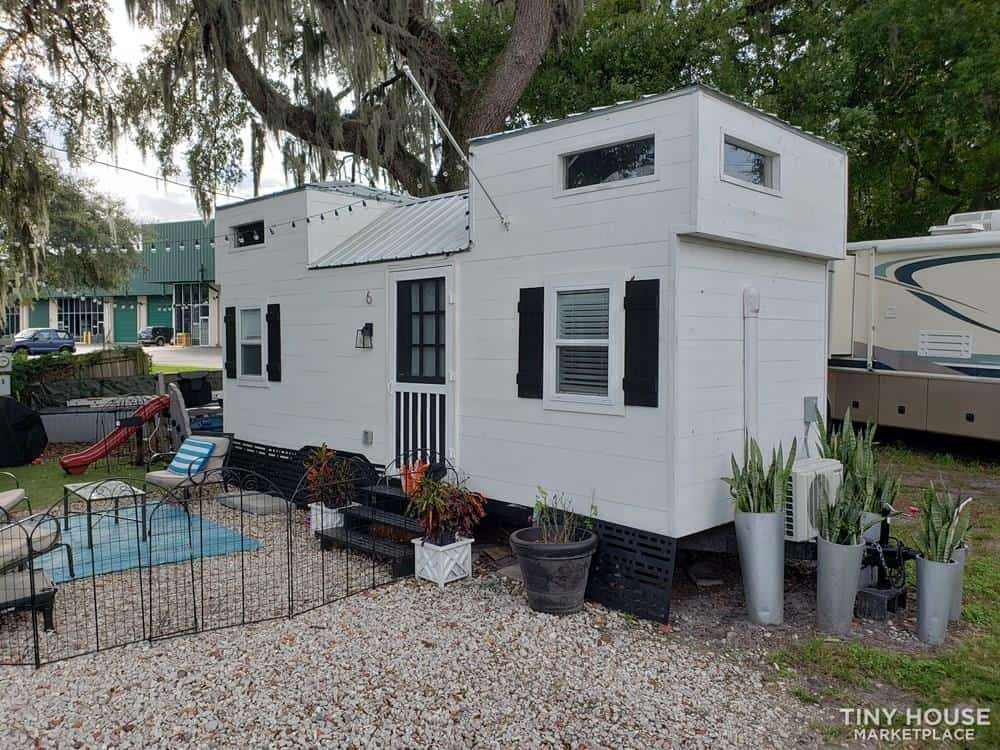 White, Farm house chic tiny house with a H-shaped roof line for sale in Orlando, Florida