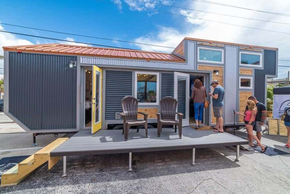 Metal exterior tiny home for sale in Florida with a front porch, lots of windows in blue sky Florida