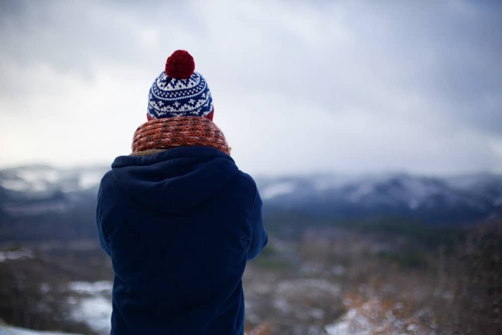Woman standing staring at the mountains in her winter gear.