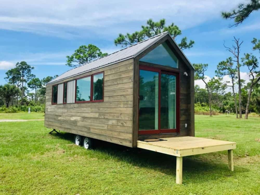 This tiny house has a metal roof and floor to roof windows on the front
