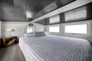 Sleeping loft with bed under windows