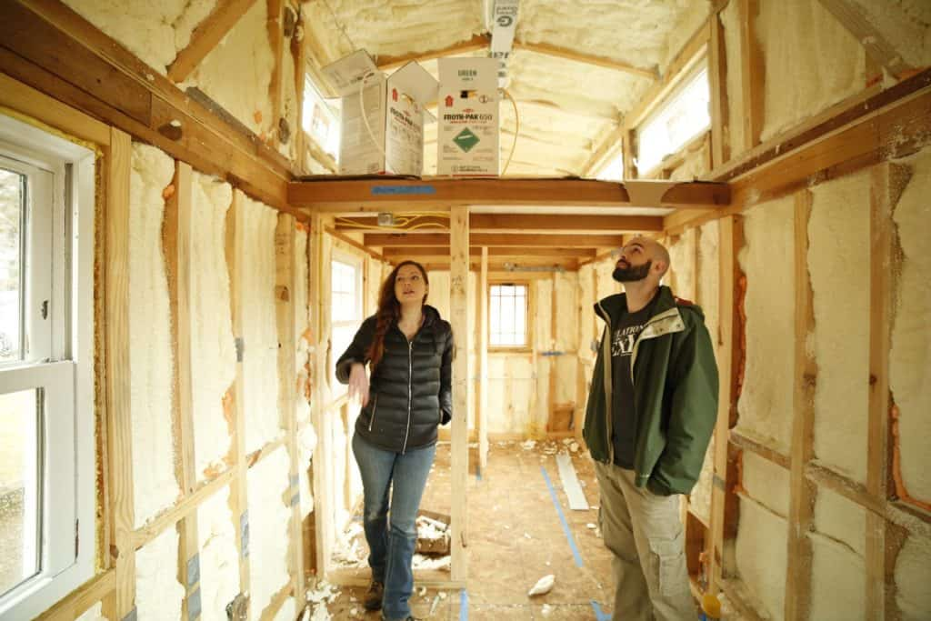 Alexis standing inside her tiny house during its build to figure out the best tiny house heating