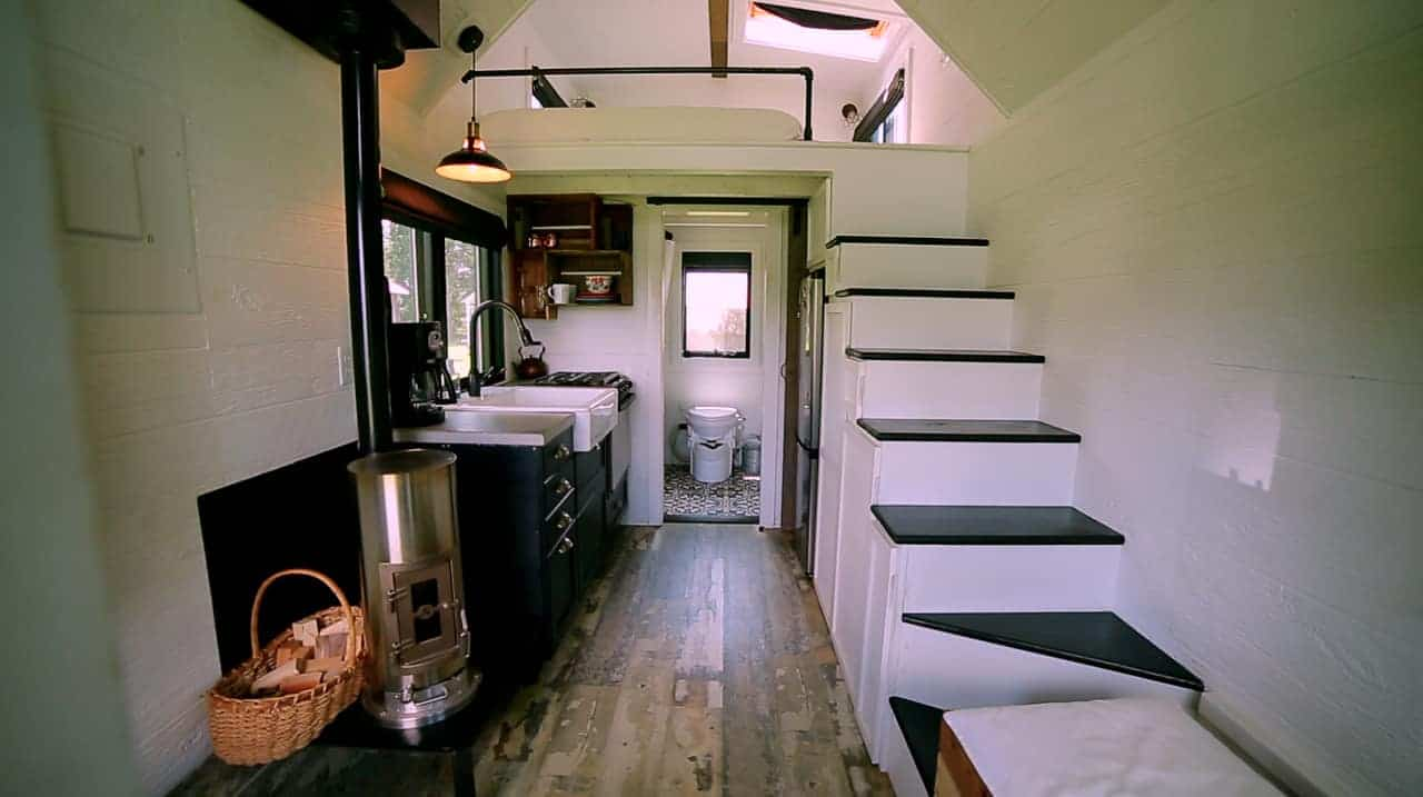 The inside of a tiny house with a tiny house wood burning stove