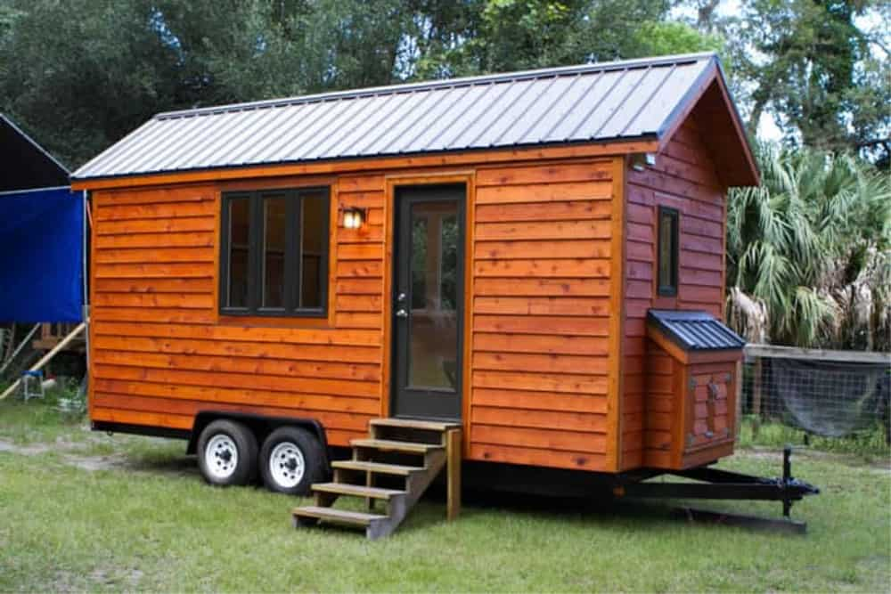 Wood siding and metal gable roof tiny home on wheels