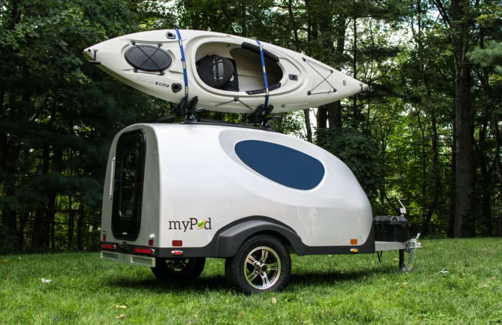 The MyPod motorcycle teardrop camper with a kayak on top parked in a forest