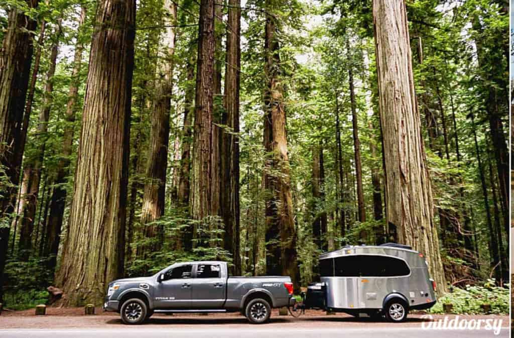 Airstream Basecamp Rental in a forest towed by a pickup truck