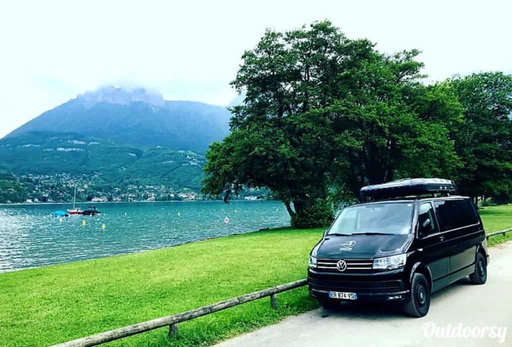 Volkswagen camper van rental in Europe parked near a beautiful lake