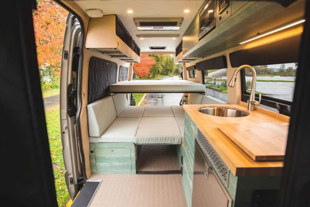 A permanent elevated van bed is the bed choice of this conversion.