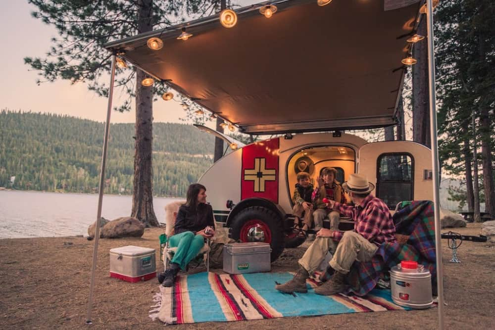Family enjoying their motorcycle teardrop camper by a lake with a lit awning