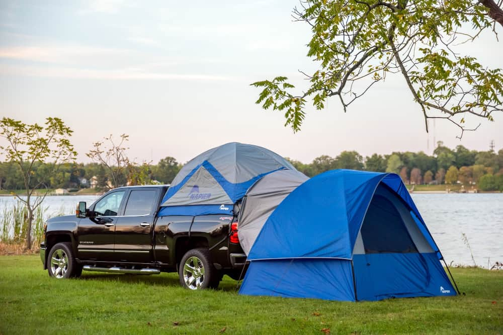 Bright blue truck bed tent camper with a ground tent extension