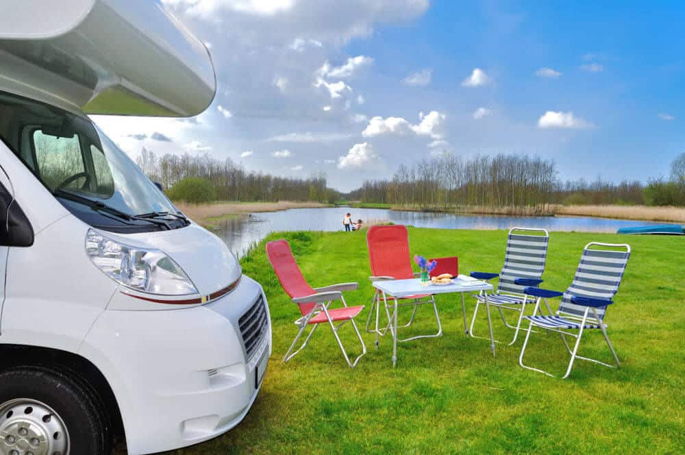 Chairs are great RV gadgets for sitting outside an RV in green grass in summer