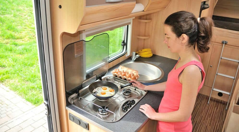 Woman cooking at her RV stove using RV gadgets and gizmos