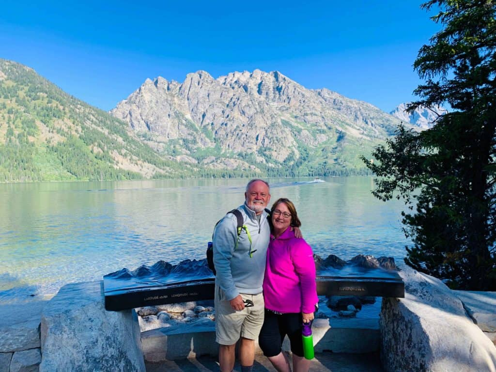 Roofnest couple standing in front of a beautiful lake and mountains