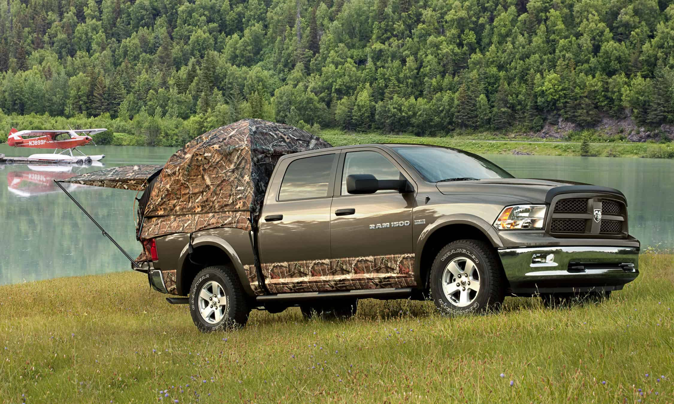 Camo truck bed tent on a pickup near a lake