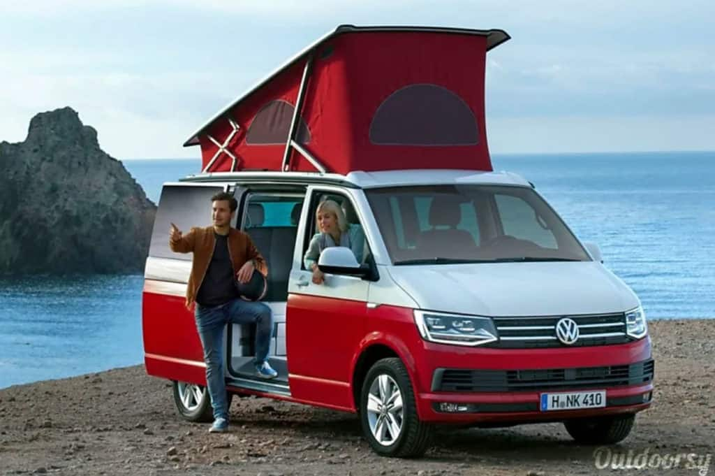 VW camper California campervan hire parked on a bluff above the sea with a ma and a woman