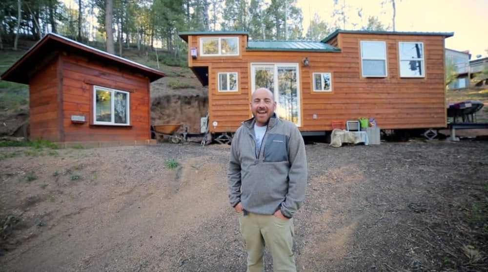 Alan stands in front of his tiny home with land