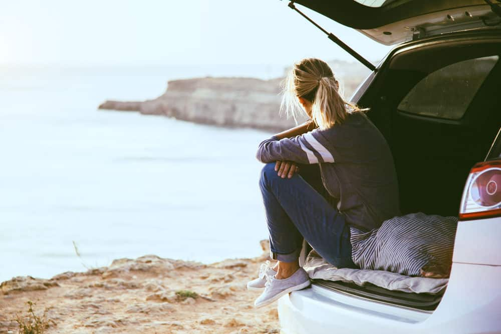 Woman in a Europe campervan hire staring the ocean