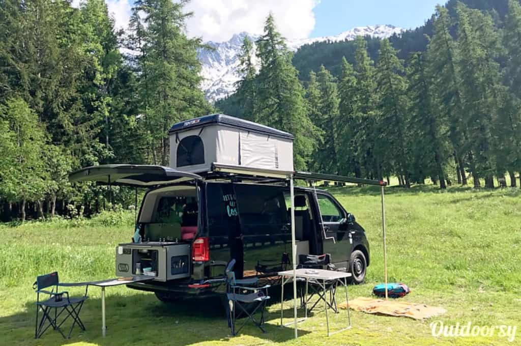 VW T6 camper van hire parked in a beautiful meadow with the roof popped up