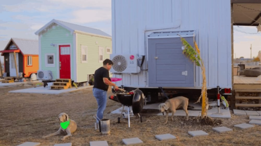 Man BBQs outside on land for tiny houses