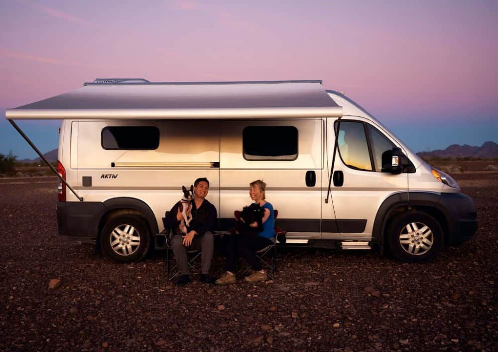 Shauna and her husband sitting outside their campervan with a cat and a dog.