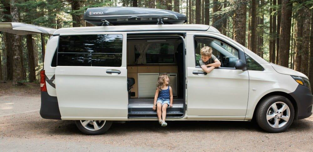 Mercedes Metris camper with side door open and two children looking out.