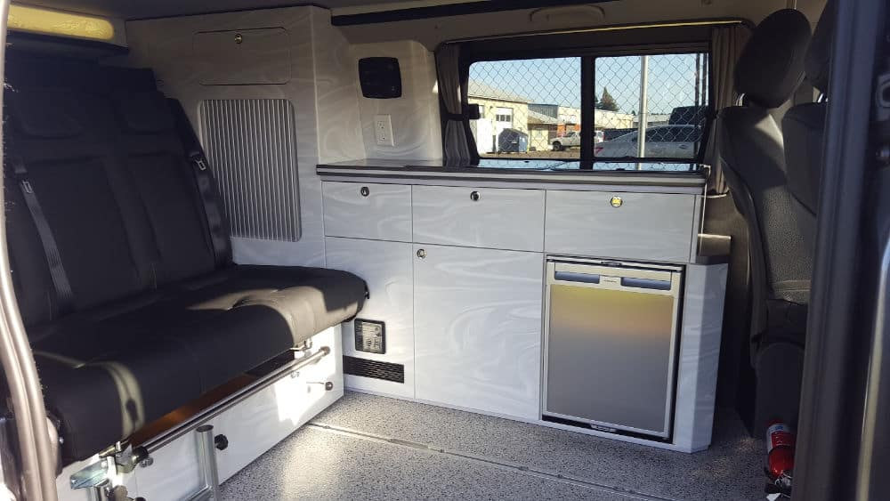 Metris camper interior with bench seat and kitchen