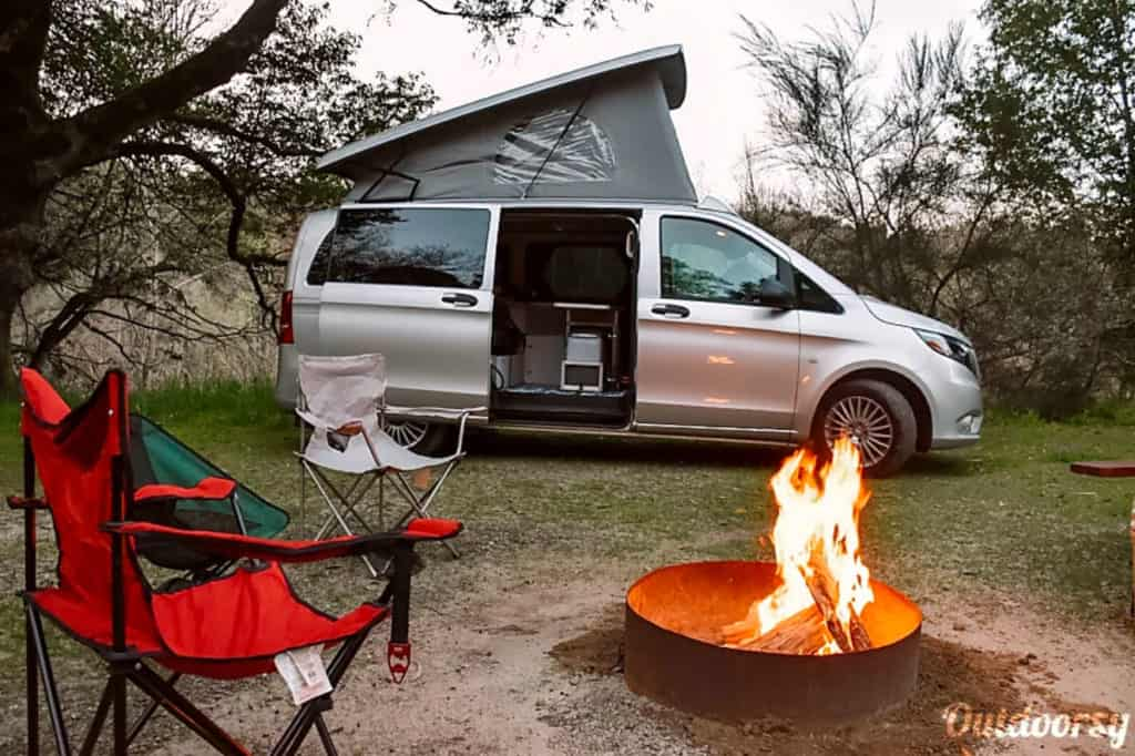 Mercedes Metris camper with side door opened and campfire and camp chairs.