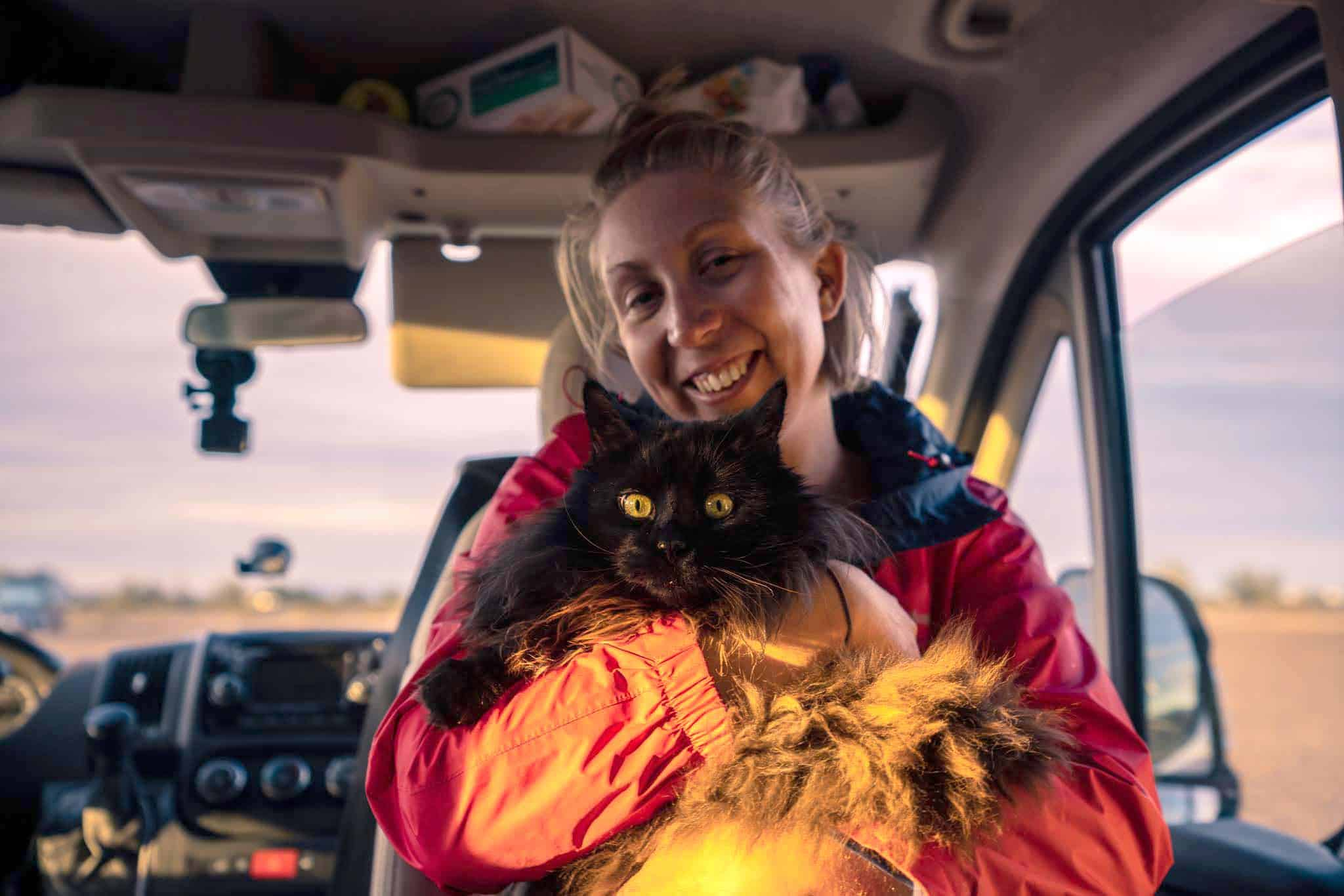 Parker the cat and Shauna in the front of their campervan