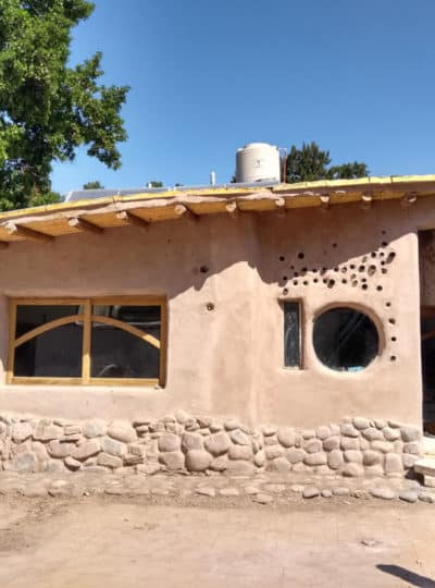 A cute cob house with a round and rectangular window