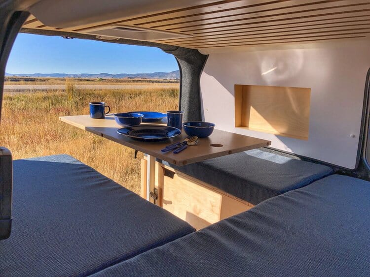 A table set with plates and cups that drops down into a campervan bed