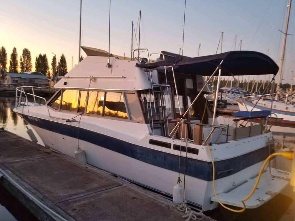 Liveaboard trawler parked at a dock at sunset.