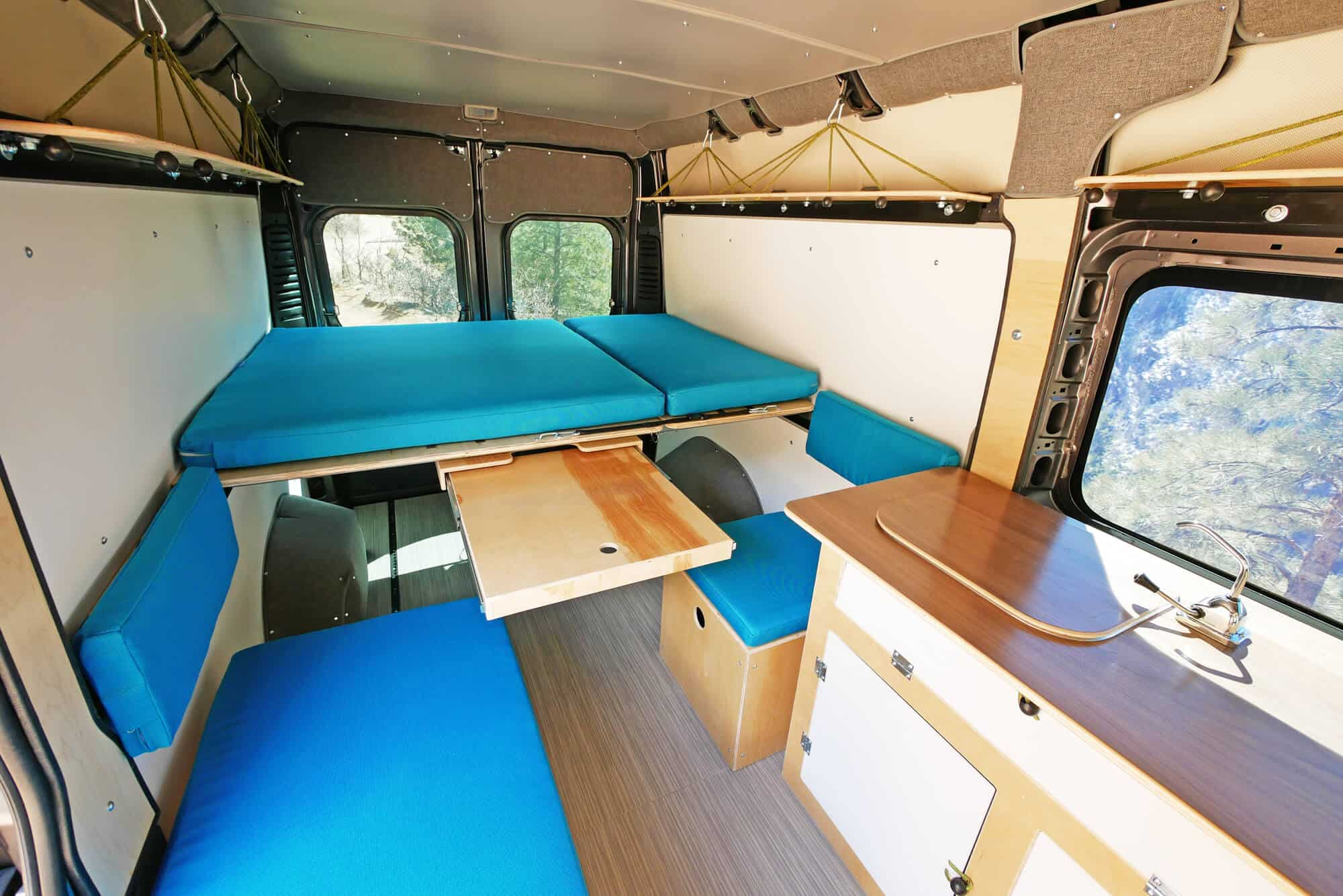 Bright blue campervan bed design with garage underneath