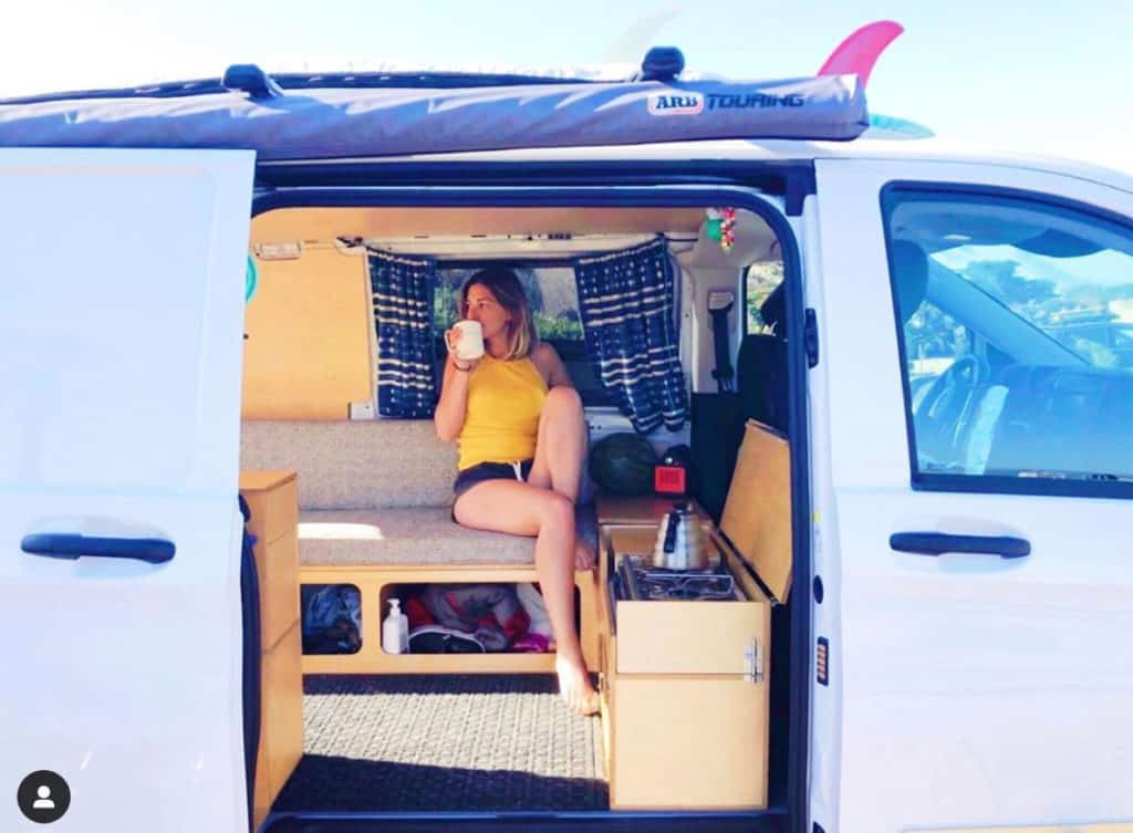 Woman sitting inside a Mercedes Metris conversion drinking a hot beverage