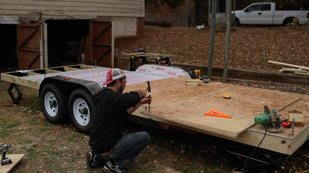 A man works on his tiny house trailer.