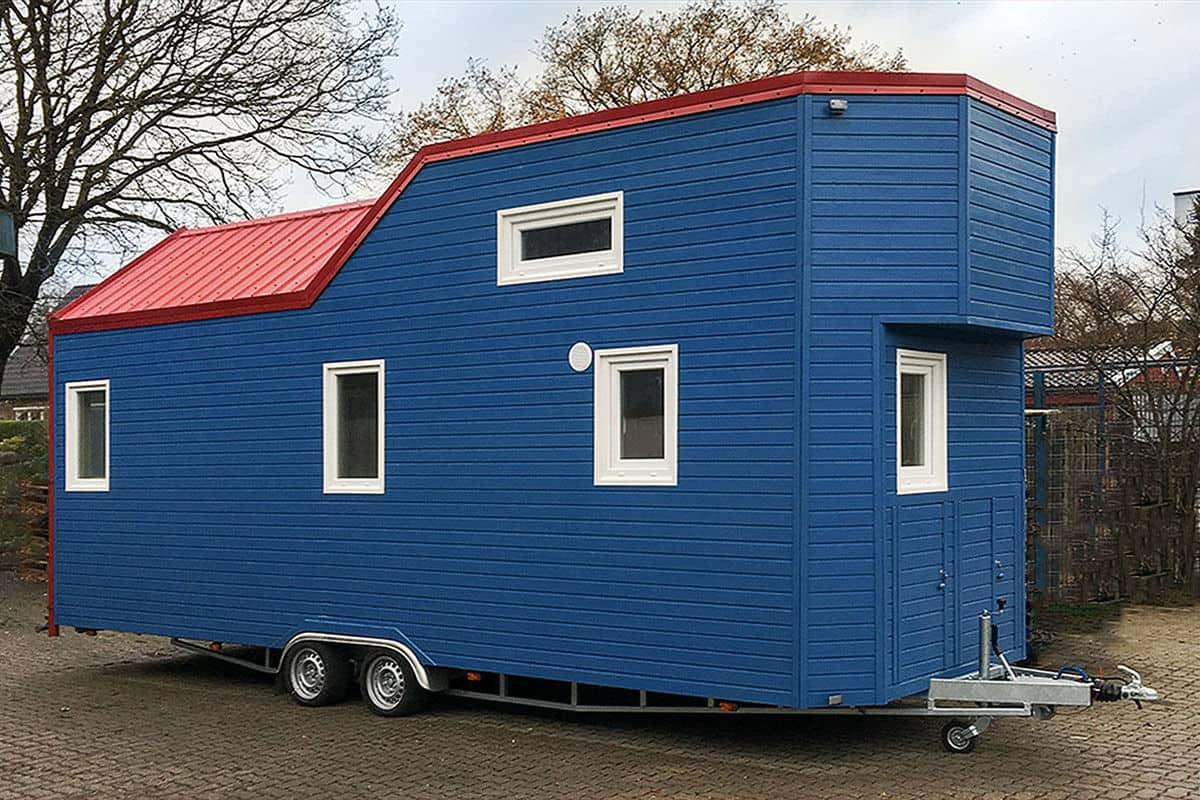 blue tiny house on a tiny house trailer