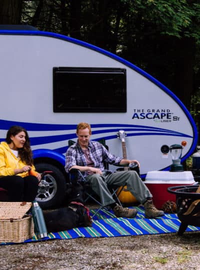 Couple sits outside their ultra lightweight travel trailer under 2000lbs.