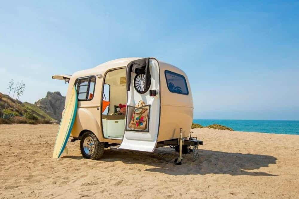 The Happier Camper setup on a beach rocking those retro vibes is one of many easy travel trailers under 2,000 pounds you can tow