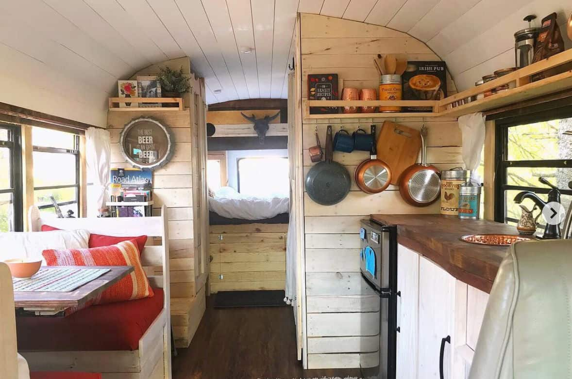 Short bus camper interior with kitchen, bedroom and living room