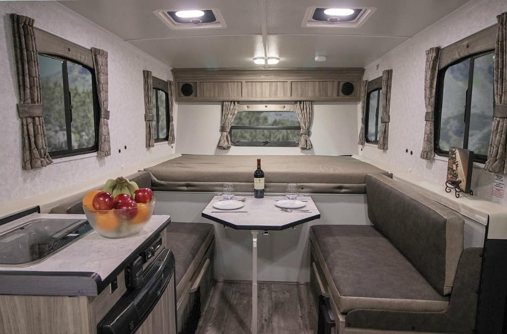 TrailManor pop up camper interior with bed and dinette.