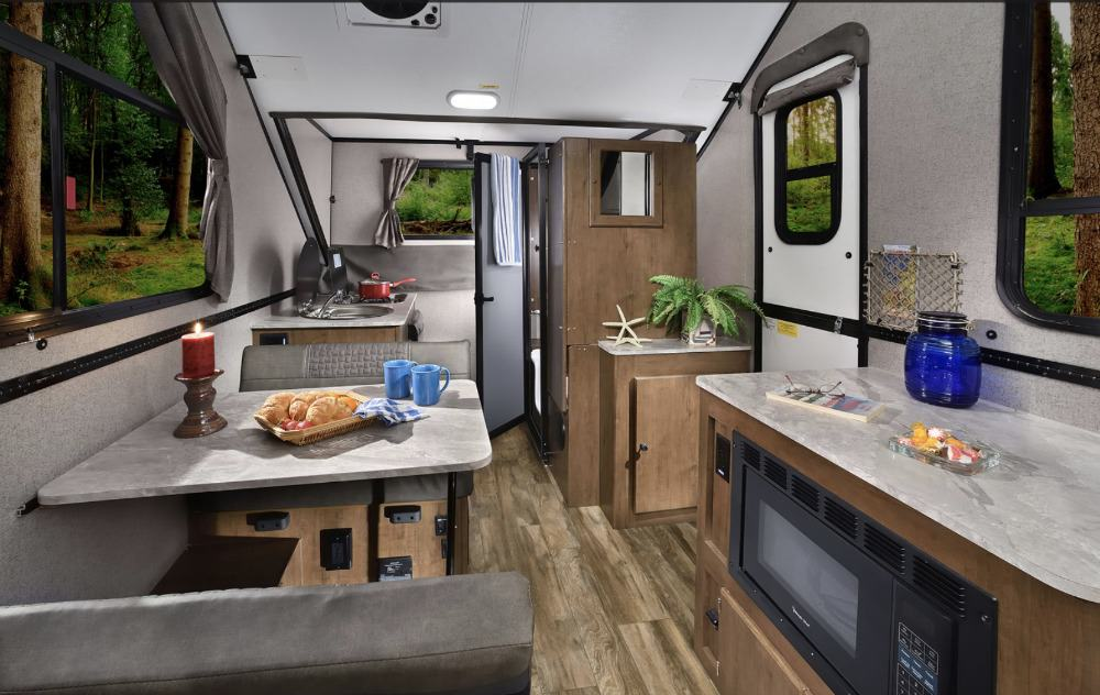 Spacious Flagstaff hard side pop up camper interior with dinette, counter space and sink.