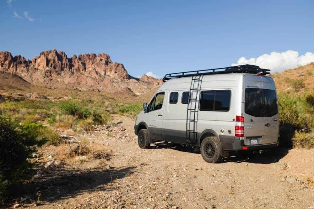 A Sportsmobile custom Sprinter van conversion parked in the desert
