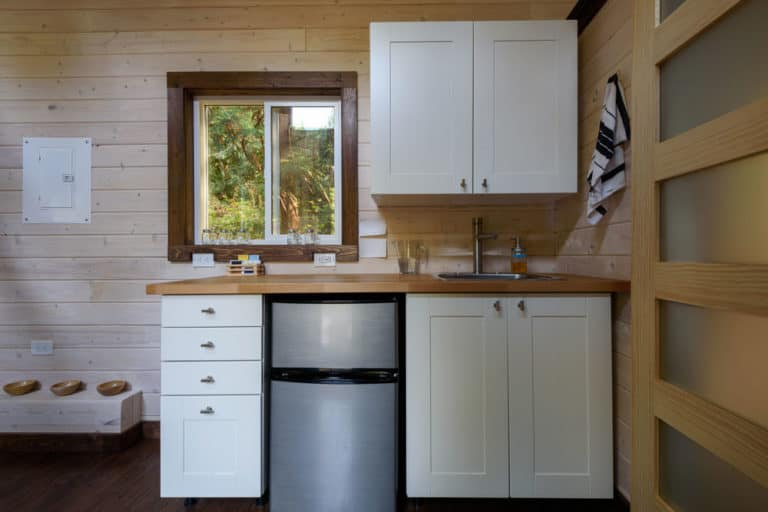 tiny house appliances like a fridge and a sink in a tiny kitchen