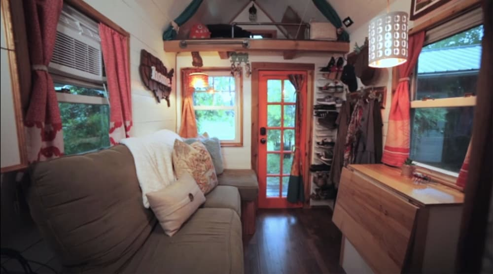 Tiny home living area with a tiny house couch, space saving shoe storage and fold down table.