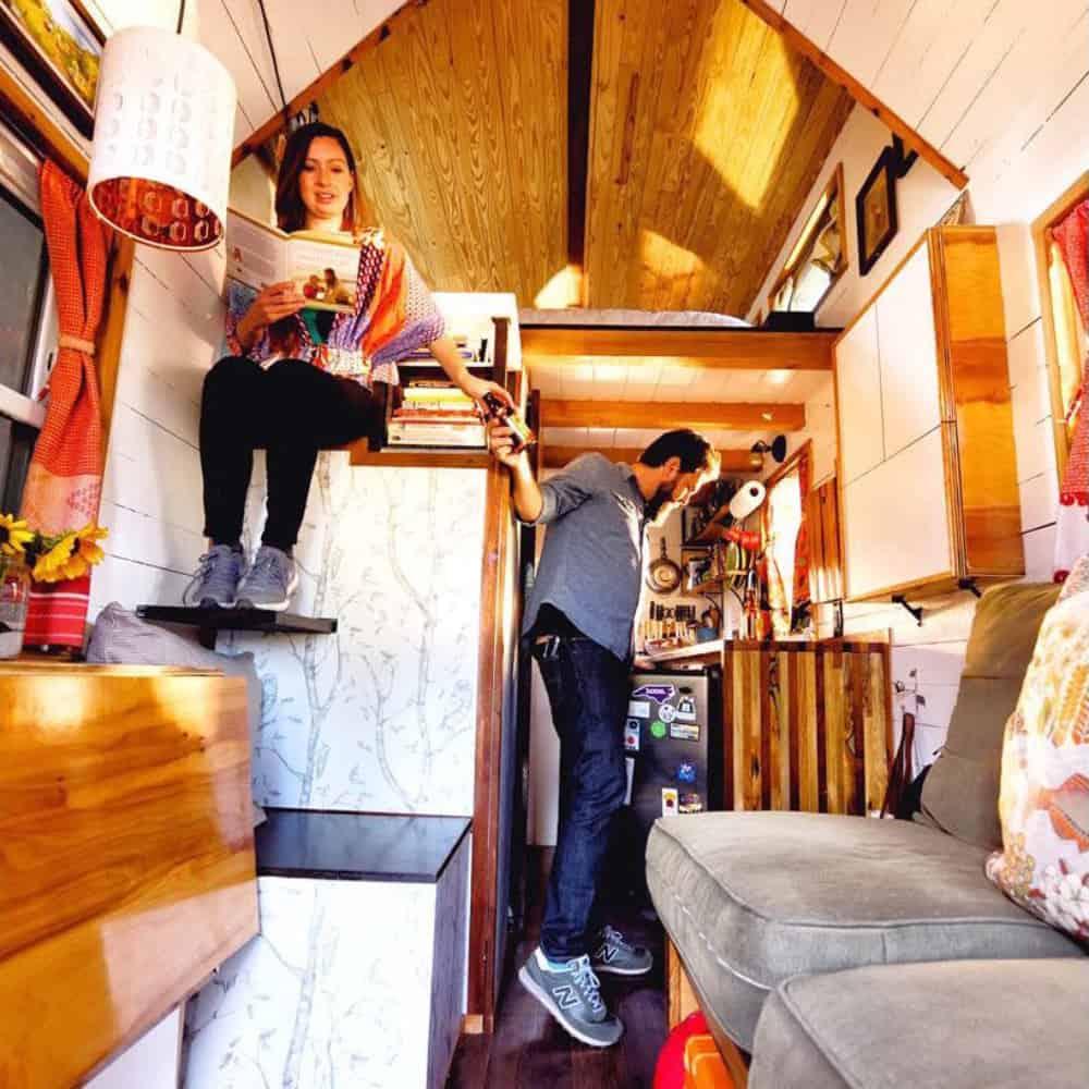 Couple taking advantage of their versatile tiny house furniture.