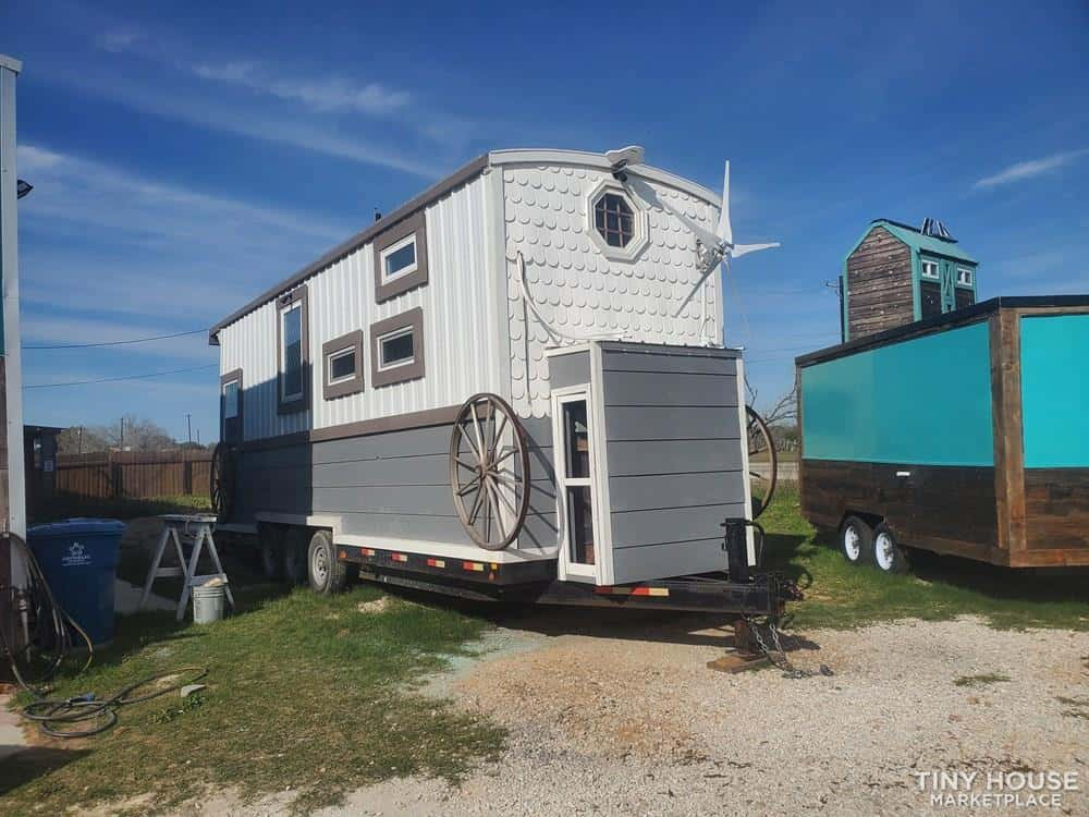 The grey and white Infinity tiny house for sale in Texas sits on a lawn next to other THOWs.