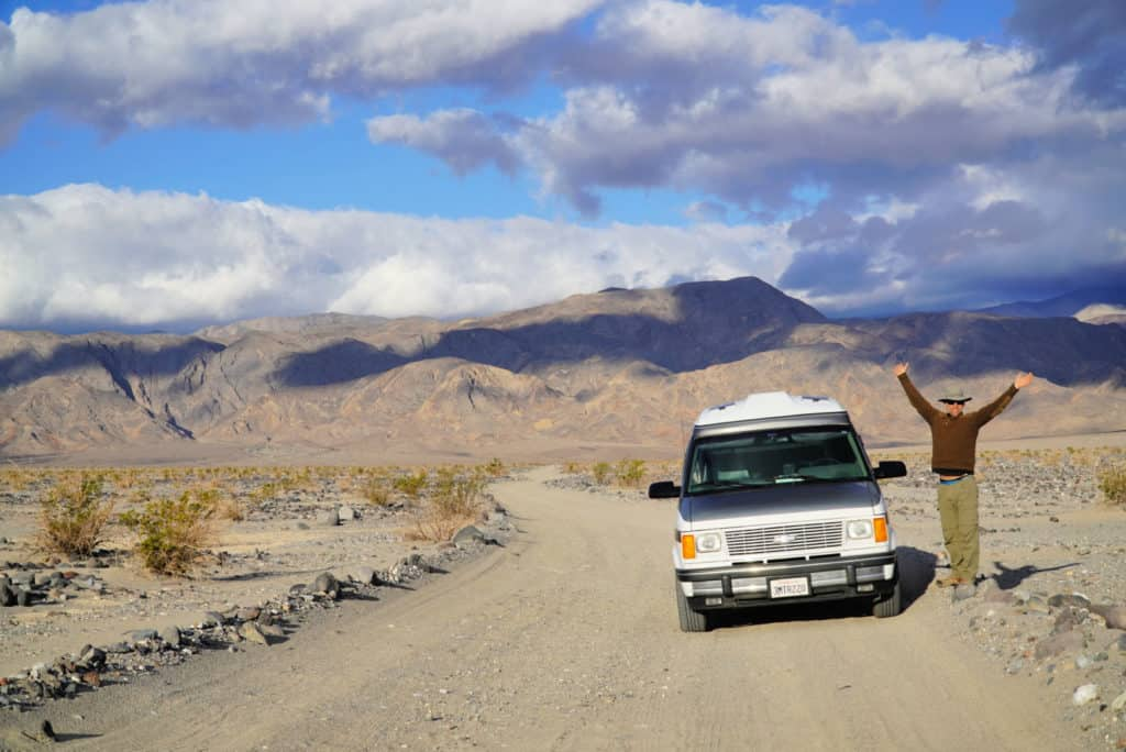 Chevy Astro van parked on a dirt road leading to free camping in Death Valley