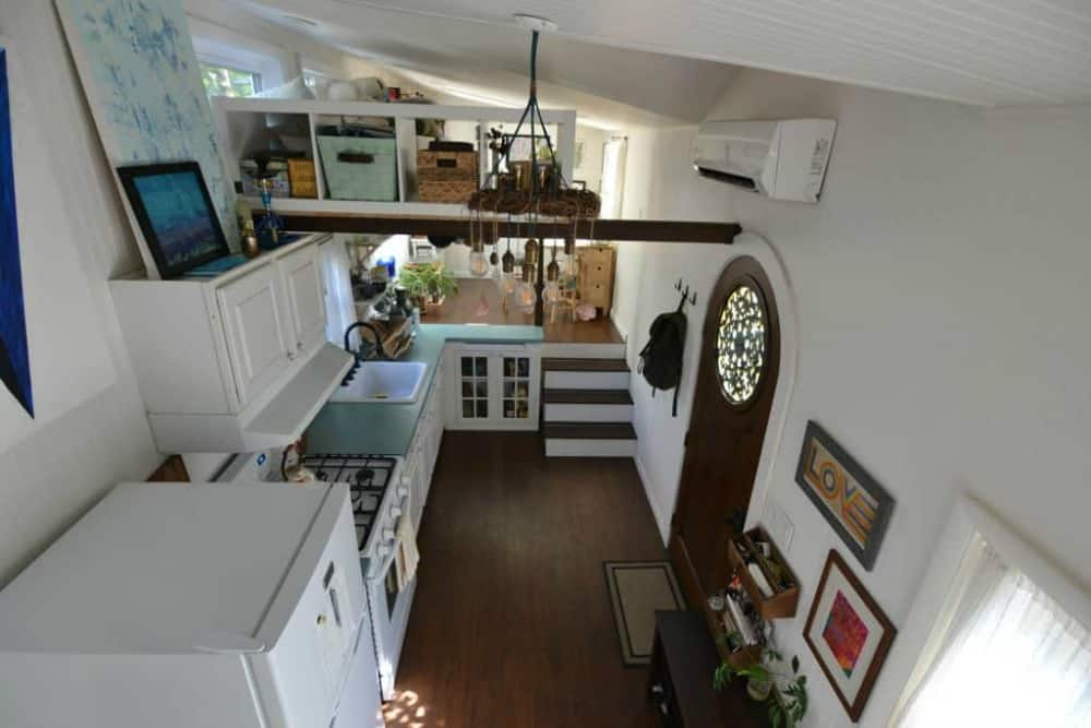 Interior view of home built with Desiderata tiny house floor plans includes view of kitchen and loft space.