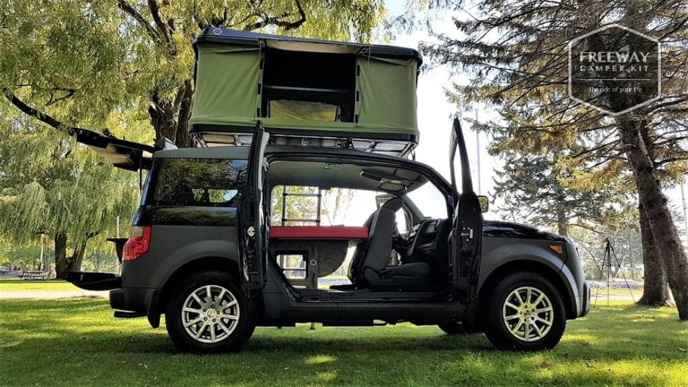 Honda Element with a rooftop tent and a bed inside, a roomy car to live in