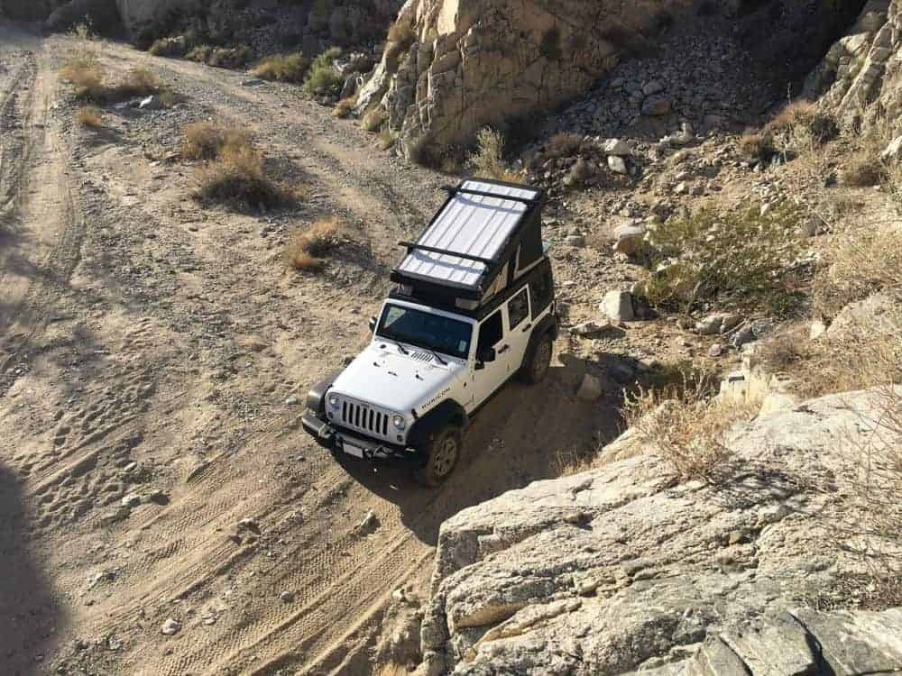 Jeep with a pop-up parked in the desert, great for living in a car and off-roading
